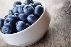 Fresh blueberries in white bowl on wood table Stock Images