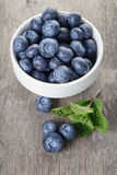 Fresh blueberries in white bowl on wood table Royalty Free Stock Photo