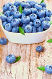 Fresh blueberries. In a white plate on a wooden background Stock Image