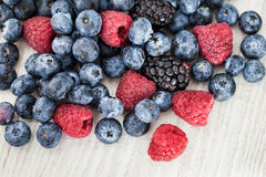 Fresh blueberry, blackberry and raspberry. On wooden table Stock Images