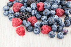 Fresh blueberry, blackberry and raspberry. On wooden table Royalty Free Stock Photo