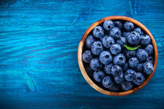Fresh blueberry. With drops of water in wooden bowl on blue  background. Top view. Concept of healthy and dieting eating Stock Photos
