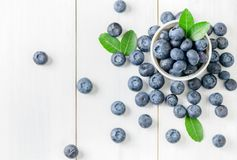 Fresh blueberry fruits with leaf on white glass. And white wood background,top view and copy space, healthy friuts concept stock photography