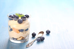Fresh blueberry layered desert with mascarpone cream and cookies. In glass stock image
