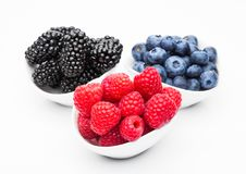 Fresh blueberry raspberry and blackberry in bowl. Fresh blueberry raspberry and blackberry in white bowl closeup on white background Stock Image