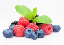 Fresh blueberry raspberry and blackberry with mint. Leaf closeup on white background Stock Photos
