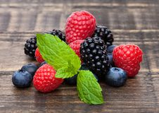 Fresh blueberry raspberry and blackberry with mint. Leaf closeup on wooden  background Stock Image