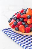 Fresh blueberry, strawberry and rasberry. On wood plate stock photos