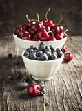 Fresh blueberry and sweet cherry in bowls Royalty Free Stock Photo