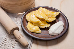 Fresh boiled varenyky or dumpling with cottage cheese or curd on. Fresh boiled homemade ukrainian dumplings with cottage cheese or curd and butter on clay plate Stock Photo