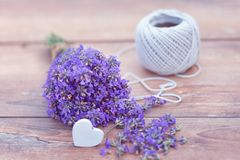 Fresh bouquet of lavender, hemp ball and a heart on brown wooden background. Stock Photography