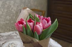 Fresh bouquet of pink tulips wrapped in papper at home interior. stock images
