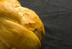 Loaf of white wheat bread. Fresh braided loaf of white wheat bread on black background royalty free stock photo