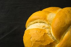 Loaf of white wheat bread. Fresh braided loaf of white wheat bread on black background stock photo