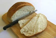 Fresh Bread. Sliced loaf of bread with knife on cutting board Royalty Free Stock Photography