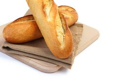 Fresh bread. Close up of two fresh long narrow french baguettes placed on fabric mat over wooden chopping board on white background Royalty Free Stock Photos