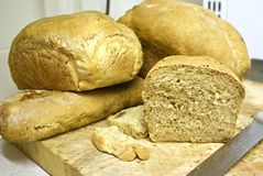 Fresh bread. Several loaves of freshly baked crusty bread with rustic background and knife stock photography