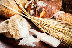 Fresh bread and baking ingredients in rustic setting Stock Images