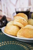 Fresh bread buns piled up, elegant white plate sitting on green table cloth, restaurant bakery concept Stock Photo