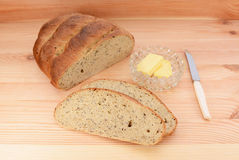 Fresh bread with butter and knife on a wooden table Royalty Free Stock Images