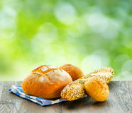 Fresh bread and checkered napkin on wooden table on rural backgr Royalty Free Stock Photo
