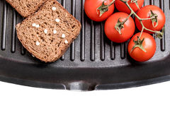 Fresh bread and cherry tomatoes on a grill pan Stock Photos