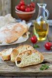 Fresh bread ciabatta. And olive oil, cherry tomatoes Stock Photo