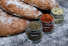 Fresh  bread and different spicies in jars. Wooden background Royalty Free Stock Photography