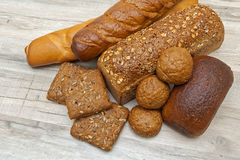 Fresh bread of different varieties on wooden background Royalty Free Stock Images
