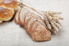 Fresh bread with ears of wheat. Fresh bread with ears of wheat on the canvas Royalty Free Stock Image
