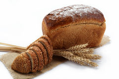 Fresh bread with ears of wheat. Fresh bread with ears of wheat on the canvas Stock Photography