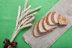 Fresh bread with ears of wheat on a canvas. Fresh bread with ears of wheat on a green canvas Stock Photos