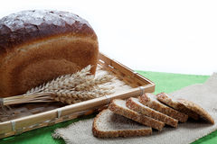 Fresh bread with ears of wheat on a canvas. Fresh bread with ears of wheat on a green canvas Royalty Free Stock Images