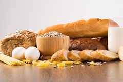 Fresh bread, eggs and glass of milk and grains. Stock Photos