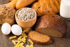 Fresh bread, eggs and glass of milk and grains. Royalty Free Stock Image