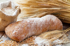Fresh bread, flour and wheat ears on wooden table. Stock Image