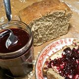 Fresh bread and homemade fruit preserve. Slice of freshly made grainy bread, with country style plate and board, home made preserve, butter and jam spoon royalty free stock photos