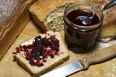 Fresh bread and homemade fruit preserve. Slice of freshly made grainy bread, with country style plate and board, home made preserve, butter and jam spoon Royalty Free Stock Photography