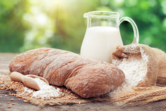 Fresh bread, jug of milk, sack of flour and wheat ears. On wooden table Royalty Free Stock Photos