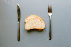 Fresh bread lies on gray table between fork and knife Stock Images