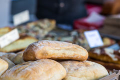 Fresh bread. Loaves of flat bread at a baker's stall. Other pastries with signage out of focus in the background stock photo
