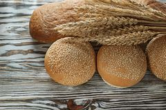 Fresh bread long loaf wheat ears on wooden surface Royalty Free Stock Photo