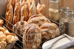 Fresh bread in metal basket in bakery on wooden background Royalty Free Stock Images