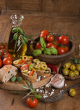 Fresh bread with olives, tomatoes, spices and olive oil on an ol Royalty Free Stock Photos