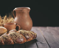 Fresh bread with pottery on a wooden table. Royalty Free Stock Image