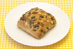 Fresh bread with pumpkin seeds. Pipes pumpkin bread, presented on plate on tablecloth background Stock Images