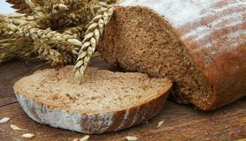 Fresh bread and ripe wheat. On the wooden board Stock Photos