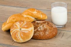 Fresh bread, rolls and a glass of milk Royalty Free Stock Photos