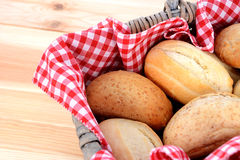 Fresh bread rolls in a rustic picnic basket. Detail of fresh bread rolls in a rustic picnic basket lined with red gingham Stock Photography