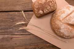 Fresh bread. Rustic bread and wheat on an old vintage planked wood table Stock Images